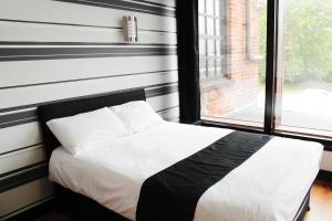 A bed or beds in a room at Cornmill Hotel