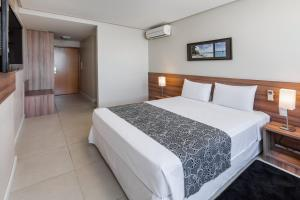 A bed or beds in a room at Days Inn by Wyndham Linhares