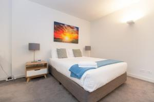 A bed or beds in a room at Southern Cross Serviced Apartments