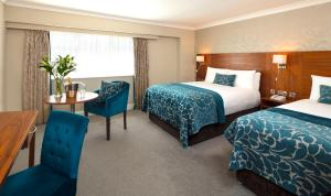 A bed or beds in a room at The Royal Hotel & Leisure Centre