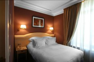 A bed or beds in a room at Hôtel Princesse Flore