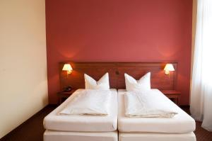 A bed or beds in a room at City Hotel garni