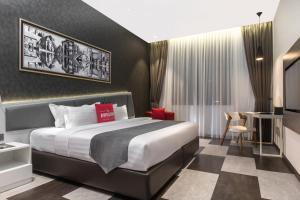 A bed or beds in a room at Iconic Hotel