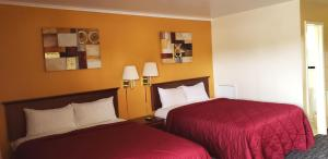 A bed or beds in a room at Super 7 Motel