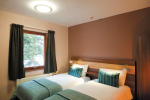 A bed or beds in a room at The Cedars Hotel