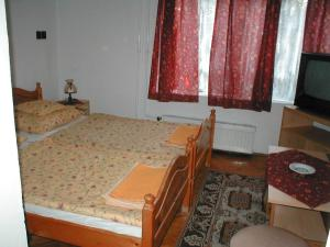 A bed or beds in a room at Krisztina Panzió