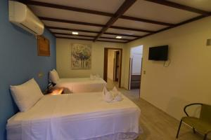 A bed or beds in a room at Porto Preguiças Resort