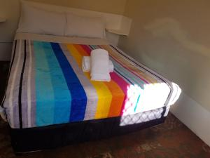 A bed or beds in a room at El Lago Tourist Park