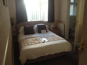 A bed or beds in a room at Bure Lodge