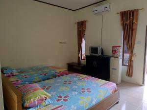 A bed or beds in a room at Putra Sindang Asih