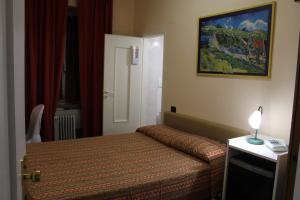 A bed or beds in a room at Hotel Agnello d'Oro Genova