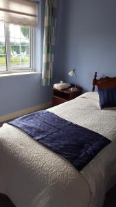 A bed or beds in a room at Coolbawn Lodge Farmhouse