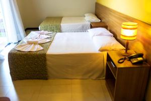 A bed or beds in a room at Hotel Girassol All Inclusive