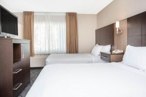 A bed or beds in a room at Baymont by Wyndham San Diego Downtown
