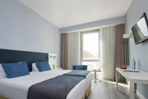 A bed or beds in a room at Hotel Faro & Beach Club