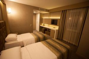A bed or beds in a room at Giresun Sedef Hotel