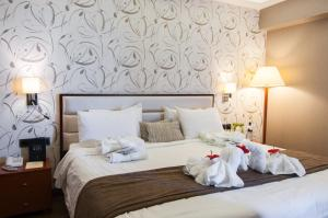 A bed or beds in a room at Palatino Hotel