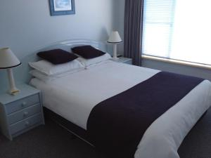A bed or beds in a room at Breakers Apartments
