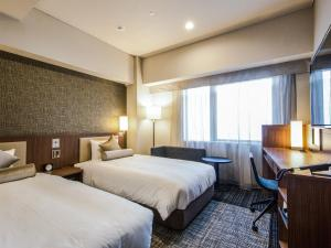 A bed or beds in a room at HOTEL UNIZO Osaka Shinsaibashi