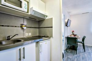 A kitchen or kitchenette at Zenitude Hôtel-Résidences Bordeaux Aéroport Mérignac