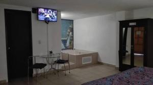 Una televisión o centro de entretenimiento en Hotel Ollin Teotl