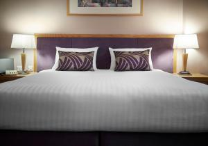 A bed or beds in a room at The Suites Hotel & Spa Knowsley - Liverpool by Compass Hospitality