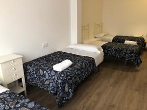A bed or beds in a room at Albergue-Pensión Cabo da Vila