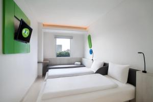 A bed or beds in a room at POP! Hotel Pemuda Semarang