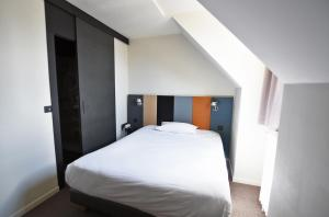 A bed or beds in a room at Citotel Hôtel De Harlay