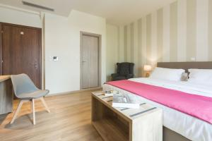 A bed or beds in a room at Hotel @Syngrou Fix