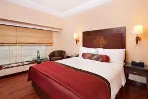 A bed or beds in a room at The Lalit Ashok