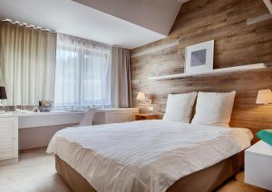 A bed or beds in a room at Cihelny Golf & Wellness Resort