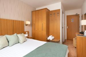 A bed or beds in a room at The Lodge In The Vale