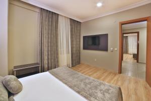 Un pat sau paturi într-o cameră la Sanli Suite Hotel