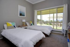 A bed or beds in a room at Hideaway - Pacific Palms