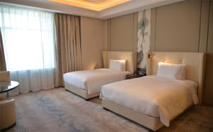 A bed or beds in a room at Hilton Urumqi