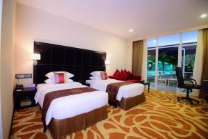 A bed or beds in a room at Taw Win Garden Hotel