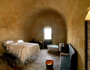 A bed or beds in a room at Sextantio Le Grotte Della Civita