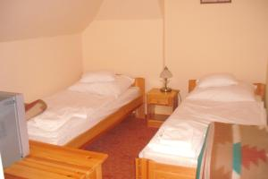 A bed or beds in a room at Lovas Udvarház Panzió