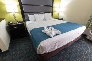 A bed or beds in a room at Days Inn & Suites by Wyndham Commerce