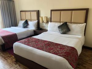 A bed or beds in a room at The Chariot Resort and Spa