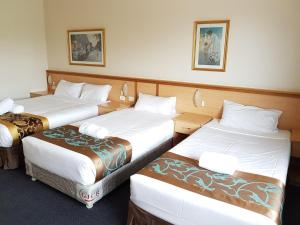 A bed or beds in a room at El Lago Waters Motel