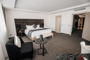 A bed or beds in a room at Grand Mogador City Center Casablanca