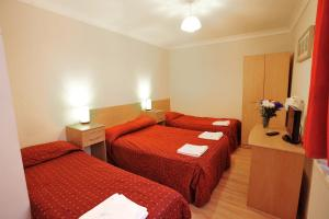 A bed or beds in a room at Elmwood Hotel
