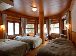 A bed or beds in a room at Hakuba Meteor Lodge