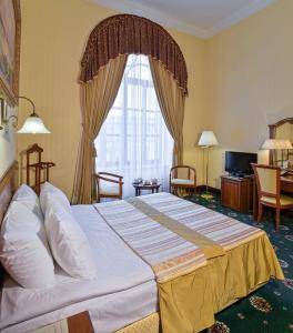 A bed or beds in a room at Ayvazovsky Hotel