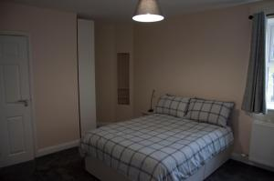 A bed or beds in a room at The Stables Guest Apartment