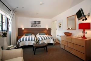 A bed or beds in a room at Trenython Manor Hotel & Spa