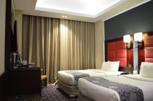 Een bed of bedden in een kamer bij Ramee Guestline Hotel
