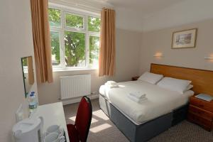 A bed or beds in a room at Clarence House Hotel